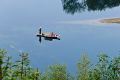 A fish boat on a lake. The picture was taken on November 2013 in Anhui Province. A fisherman is standing on his little fish boat on a lake Royalty Free Stock Image