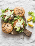 Fish burger. Burgers with tuna, avocado and mustard sauce with whole grain homemade buns on wooden cutting board on a light backgr Royalty Free Stock Image