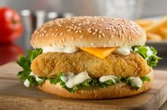 Fish burger with cheese, lettuce, and mayonnaise. A delicious crispy fish burger with cheese, lettuce, and mayonnaise Royalty Free Stock Photo