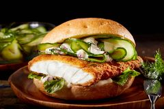 Fish burger with crumbed fillet of fish. And sliced cucumber on a crusty bun served on a plate on rustic wood background royalty free stock images