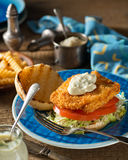 Fish Burger. A delicious home made fish burger with lettuce, tomato, and tartar sauce Stock Image
