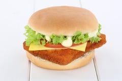 Fish burger fishburger hamburger tomatoes lettuce cheese wooden Royalty Free Stock Photography