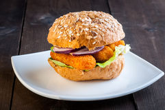 Fish burger. Burger with fish sticks on a white plate royalty free stock photography