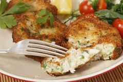 Fish cakes being eaten. Easy to make fishcakes, with steamed fish crumbled into mashed potato and parsley mix, thickened with some flour, rolled in breadcrumbs royalty free stock photos