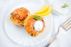 Fish cakes (cutlets). Homemade thai fish cakes (cutlets) with white sauce, dill and lemon on plate Royalty Free Stock Image