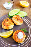 Fish cakes (cutlets). Homemade thai fish cakes (cutlets) with white sauce, dill and lemon on plate and rustic wooden table Stock Photography