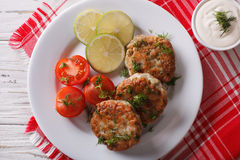 Fish cakes with dill sauce on the table close-up. Horizontal top. Hot fish cakes with dill sauce on the table close-up. horizontal view from above Royalty Free Stock Photography