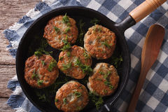 Fish cakes with herbs close-up in a pan. Horizontal top view Royalty Free Stock Images