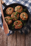 Fish cakes with herbs close-up in a pan. vertical top view Royalty Free Stock Image