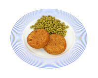 Fish cakes and peas on plate Royalty Free Stock Image