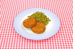 Fish cakes and peas on plate Stock Images