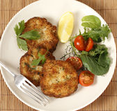 Fish cakes and salad high angle. Easy to make fishcakes, with steamed fish crumbled into mashed potato and parsley mix, thickened with some flour, rolled in royalty free stock photo