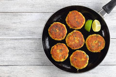 Fish cakes on skillet with lime. Delicious fresh fried fish cakes on skillet with lime slices, authentic recipe, view from above Royalty Free Stock Photo