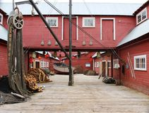 Fish Cannery Building. A red building is situated on a wharf. There is a fishing net draped over a roller on the left and a small white fishing boat in the back Royalty Free Stock Image