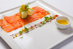 Fish carpaccio. Carpaccio of salmon on white plate Royalty Free Stock Images