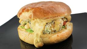 Fish cheese burger with the cheese sauce and aioli stock images