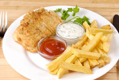 Fish and chips. White plate with fish and chips, mayo and ketchup Royalty Free Stock Photo