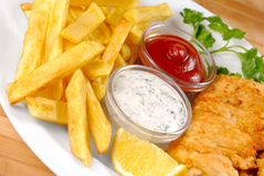 Fish and chips. White plate with fish and chips, mayo and ketchup Stock Images