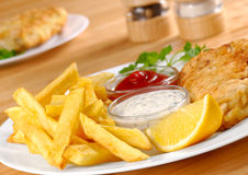 Fish and chips. Fish, chips, mayo and ketchup on the white plate Royalty Free Stock Photo