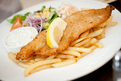 Fish and chips. On a white plate with a lemon slice on top Stock Images