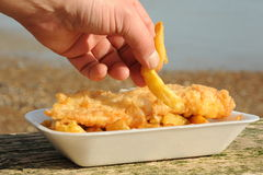 Fish and Chips. Photograph of fish and chips with a hamnd taking some chips Royalty Free Stock Images