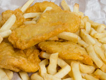 Fish and Chips. Traditional take away fish and chips in paper wrapping Royalty Free Stock Images