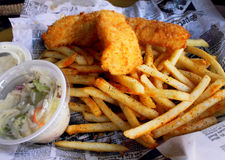 Fish & Chips Basket. Scrumptious fish and seasoned chips with slaw and tartar sauce in a basket Stock Photos