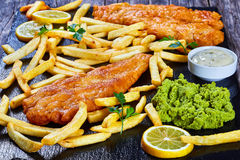 Fish and chips on black slate plate Stock Photos