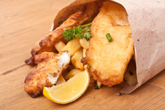 Fish and Chips in Craft paper. Fish and Chips wraped in Craft paper on a wooden table Royalty Free Stock Photos