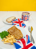 Fish and chips with a cup of tea  bread and butter and union jac. A meal of  english fish chips and peas, a slice of bread and butter, a mug of tea in a union Stock Images