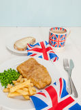 Fish and chips with a cup of tea  bread and butter and union jac. A meal of  english fish chips and peas, a slice of bread and butter, a mug of tea in a union Royalty Free Stock Photo