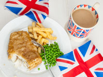 Fish and chips with a cup of tea  in a union jack mug and britis. Closeup of a meal of british  fish chips and peas and a mug of tea in a union jack mug and Royalty Free Stock Images