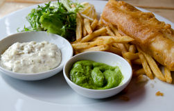 Fish and chips. A meal of fish and chips with mushy peas Royalty Free Stock Images