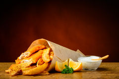 Fish and chips menu. Still life with traditional fish and chips menu, lemons and dip sauce Stock Images