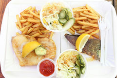 Fish and chips on paper plate takeout. Fish and chips with coleslaw, lemon and herb butter on paper plate takeout Royalty Free Stock Image