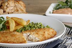 Fish chips and peas. Breaded cod fillet chips and peas on a plain white plate Stock Photo