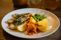 Fish and chips plate with vegetables and lemon on a plate Stock Photo