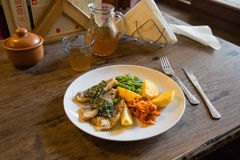 Fish and chips plate with vegetables and lemon on a plate Royalty Free Stock Image