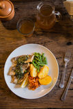 Fish and chips plate with vegetables and lemon on a plate Royalty Free Stock Images