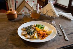 Fish and chips plate with vegetables and lemon on a plate Stock Image
