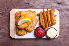 Fish and chips with potato wedge. On wooden royalty free stock image
