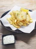 Fish and Chips with sauce dipping on wooden table Stock Photos