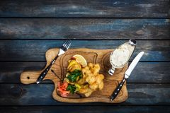 Fish and Chips with sauce tartar served with cutlery stock photo