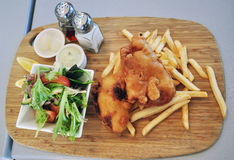 Fish and chips. Served with tartar sauce and vegetables Royalty Free Stock Photos