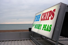 Fish & Chips Sign. Illuminated sign saying 'fish chips and mushy peas' at Brighton sea front on a gloomy day Stock Photography
