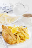 Fish and Chips Supper. Fish in batter and chips served with buttered bread and a pot of tea. Favourite British seaside supper Royalty Free Stock Photo