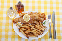 Fish and Chips. A traditional  plate of fish and chips on a yellow checkered tablecloth Stock Photos