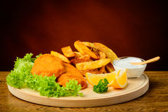 Fish and chips on a wooden plate Royalty Free Stock Photos