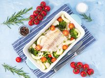 Fish cod baked in blue oven with vegetables - broccoli, tomatoes. Healthy diet food. Blue stone background, top view. Fish cod baked in blue oven with stock photos