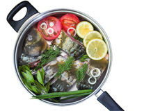 Fish and components for her preparation in a large skillet. Stock Photography